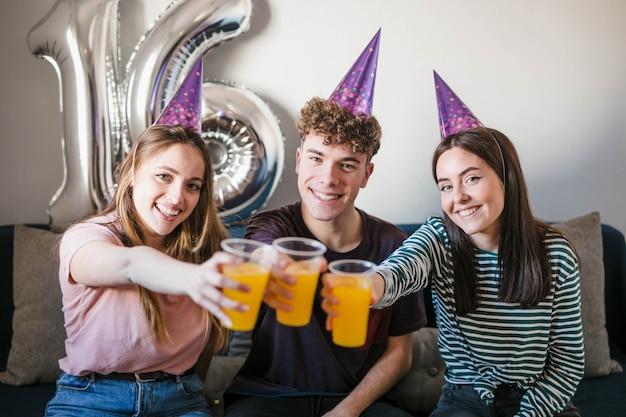 Adolescentes brindando con tazas de refrescos