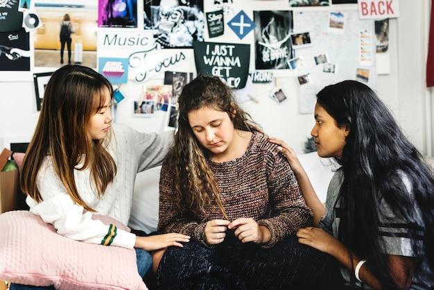 Adolescentes consolando a su amigo preocupado llorando deprimido