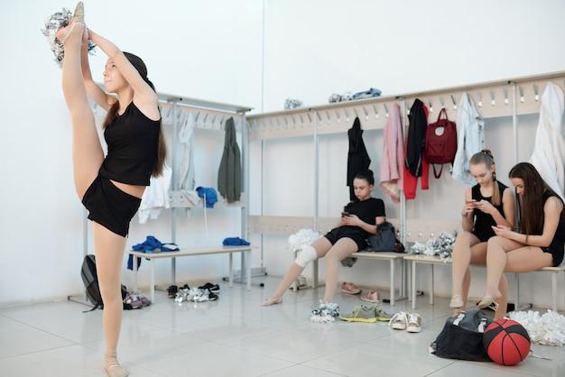 Las adolescentes decididas con pompón practicando split en el vestuario mientras sus compañeros de grupo descansando en un banco
