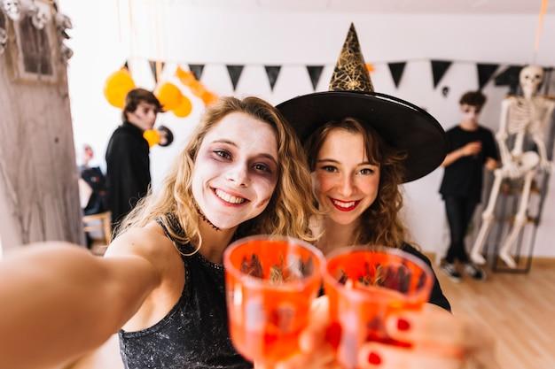 Adolescentes en disfraces de halloween en la fiesta haciendo selfie
