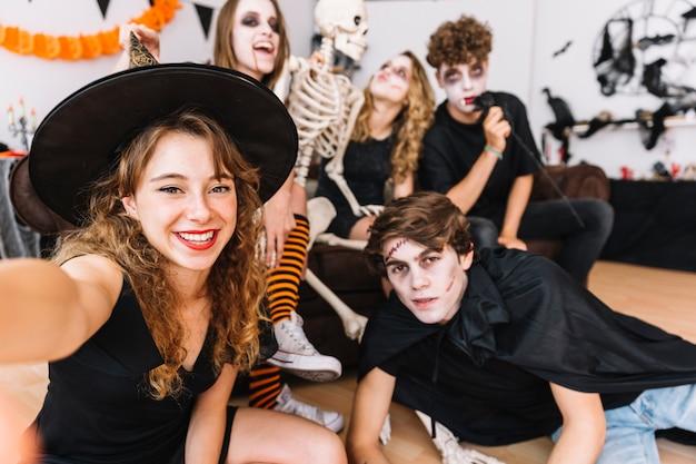 Adolescentes en disfraces de halloween haciendo selfie en piso