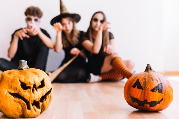 Adolescentes en disfraces de halloween sentado detrás de calabazas