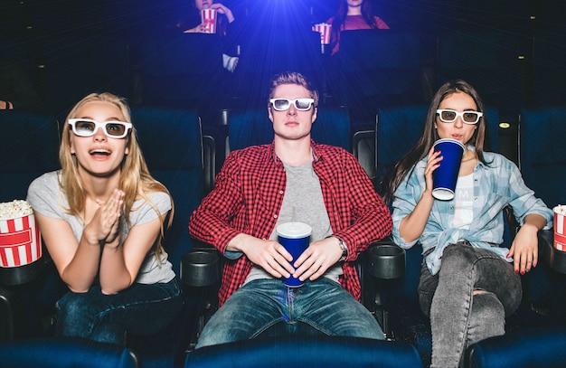 Adolescentes emocionales están sentados en sillas y viendo películas. chica rubia lo está mirando con entusiasmo. chica morena está mirando directamente y beber cola de la taza a través de paja.