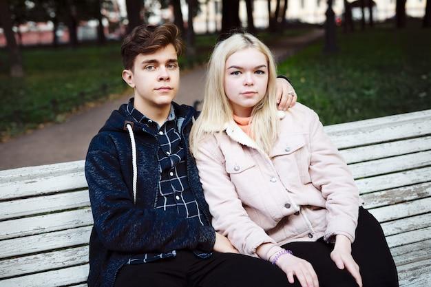 Los adolescentes enamorados se sientan en un banco del parque en otoño y miran hacia adelante