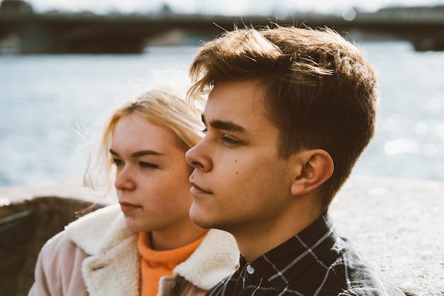 Los adolescentes enamorados se sientan frente al mar en el centro de la ciudad. concepto el primer amor adolescente,