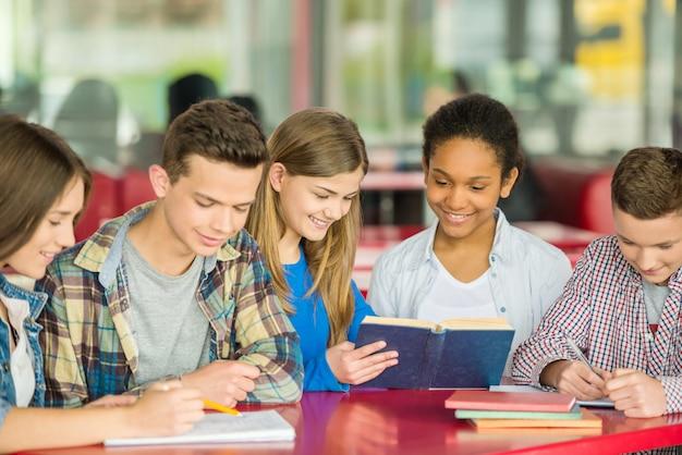 Los adolescentes están sentados en un café y mirando en el libro.