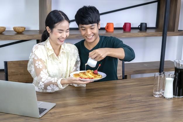 Los adolescentes están vertiendo miel sobre una tarta de fresas. Foto Premium