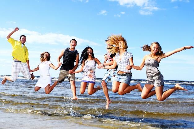 Adolescentes felices jugando en el mar