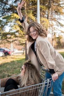 Adolescentes felices posando con carrito de compras