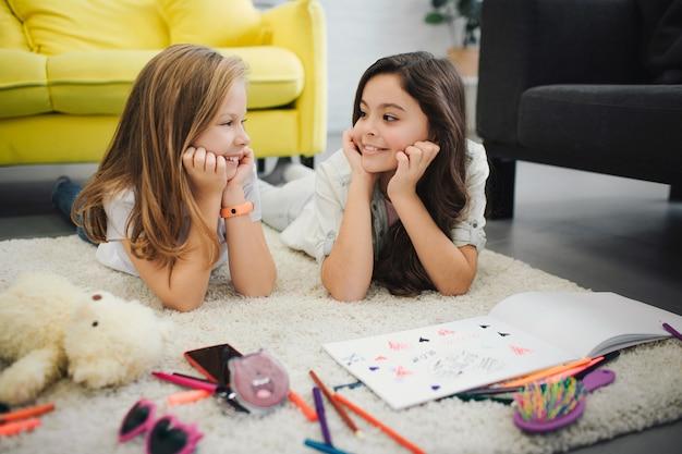 Adolescentes felices y positivas acostado en el piso y mirarse. ellos sonrien. la gente tiene equipos de dibujo en la alfombra.