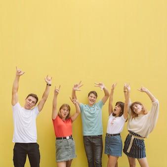 Adolescentes en el festival de música de verano que tiene buen tiempo en un fondo amarillo.