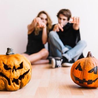 Adolescentes haciendo gestos zombie detrás de calabazas