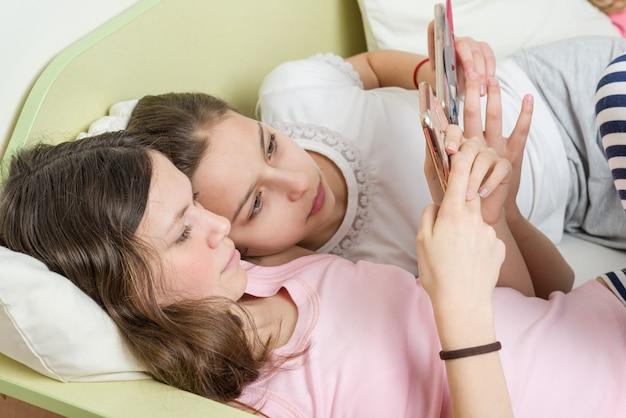 Las adolescentes con interés miran en el teléfono inteligente