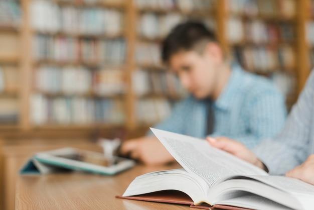 Adolescentes irreconocibles estudiando en la biblioteca
