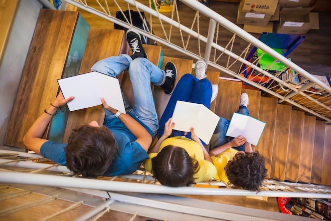 Adolescentes irreconocibles que leen en la escalera