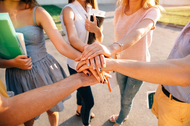 Adolescentes jóvenes equipos de estudiantes juntos manos apiladas. de cerca