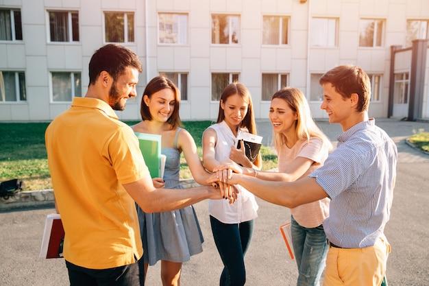 Adolescentes jóvenes equipos de estudiantes juntos manos apiladas. concepto alegre