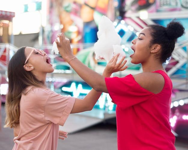 Adolescentes jugando juntos en el parque de diversiones