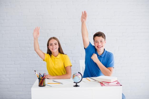 Adolescentes levantando sus manos