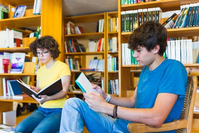 Adolescentes leyendo cerca de estanterías en la biblioteca