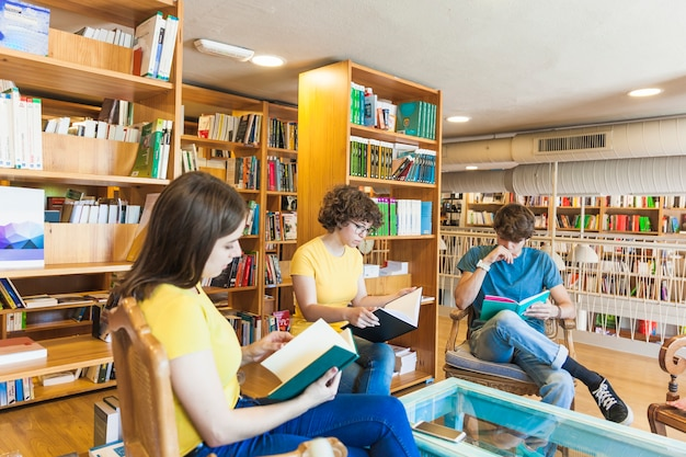 Adolescentes leyendo libros alrededor de la mesa