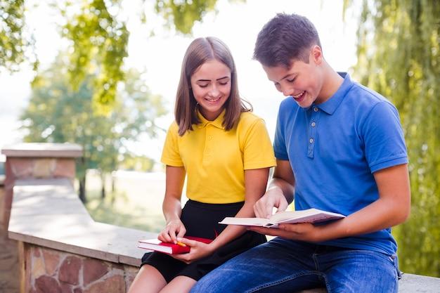 Adolescentes leyendo libros en el parque