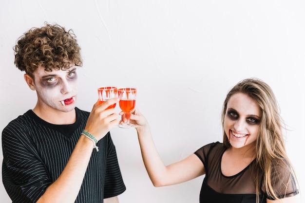 Adolescentes en maquillaje de halloween bebiendo líquido rojo