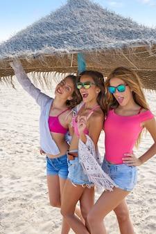 Adolescentes mejores amigas chicas bajo paraguas de paja