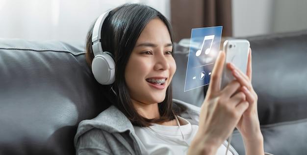 Los adolescentes modernos escuchan música con auriculares en sus teléfonos inteligentes a través de una aplicación en internet