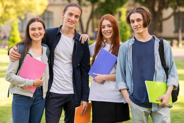 Adolescentes positivos posando juntos en la universidad