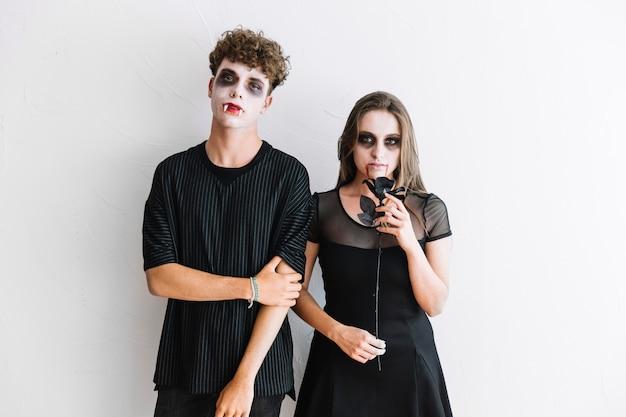 Adolescentes en ropa negra y temible vampiro sombrío de pie con rosa negro