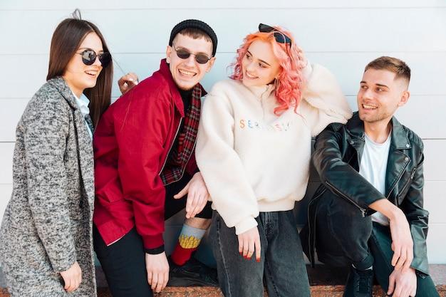 Adolescentes sentados en un banco y sonriendo