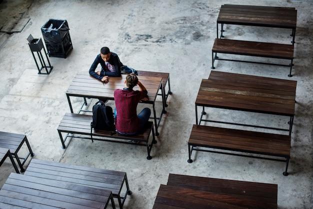 Adolescentes sentados juntos en una cantina vacía