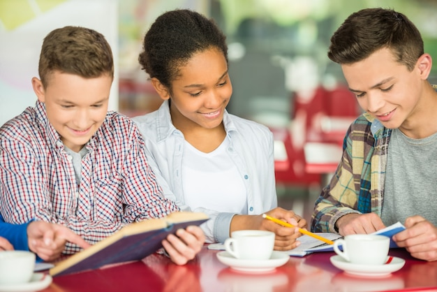Adolescentes sentados a la mesa en la cafetería estudiando y bebiendo té