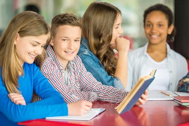 Adolescentes sentados a la mesa en la cafetería y hacer la tarea.