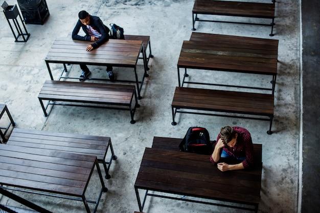 Adolescentes sentados solos en una cantina vacía