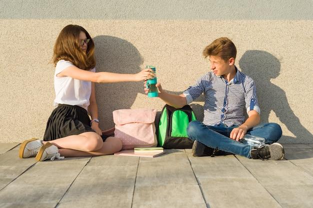 Los adolescentes se sientan en la pared gris