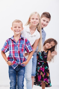 Los adolescentes sonrientes felices de pie del brazo sobre fondo blanco.