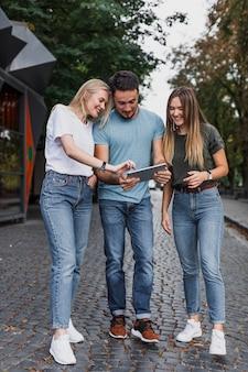 Adolescentes de tiro completo mirando en una tableta