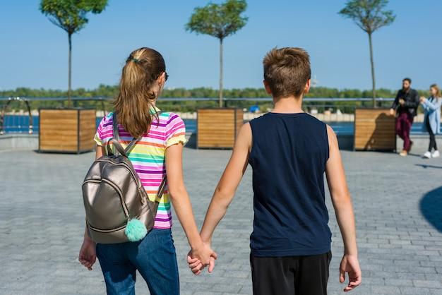 Adolescentes tomados de la mano vista trasera. amistad, primer amor.