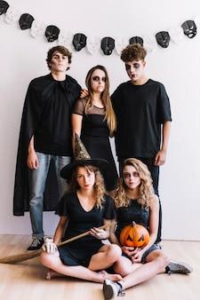 Adolescentes en trajes de halloween con escoba y calabaza