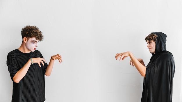 Adolescentes vestidos de negro y espantosos haciendo gestos zombie
