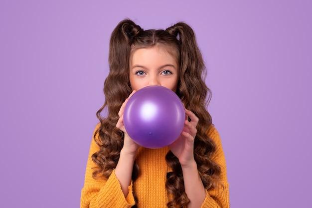 Adorable adolescente con largas coletas onduladas que sopla un globo de fiesta púrpura