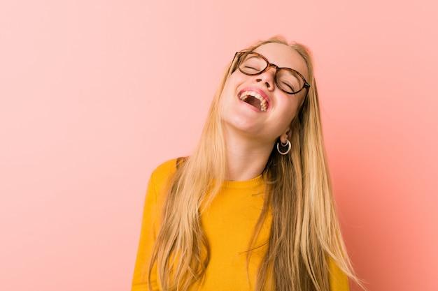 Adorable adolescente mujer relajada y feliz riendo, cuello estirado mostrando los dientes.