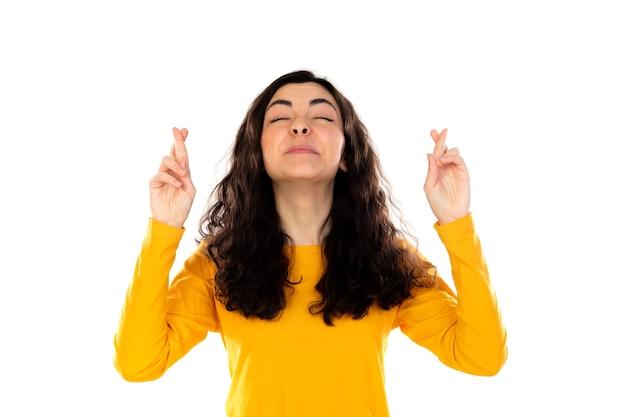 Adorable adolescente con suéter amarillo aislado en una pared blanca