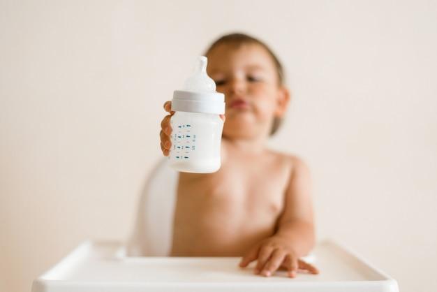 Adorable bebé bebiendo leche de una botella de botella.