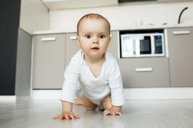 Adorable bebé gateando sobre el piso de la cocina con cara divertida