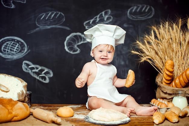 Adorable bebé en la mesa con masa
