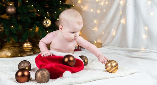 Adorable bebé con ropa de santa claus sobre un fondo de bolas de navidad