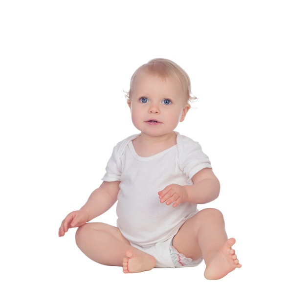 Adorable bebé rubio sentado en el suelo